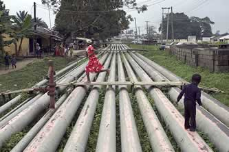 kids playing on a rack of pipelines in a residential neighborhood photo