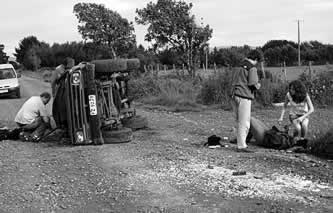 photo of a vehicle on its side, and people tending wounded on the shoulder of a dirt road