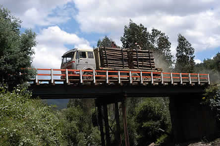photo of a logging truck crossing a bridge