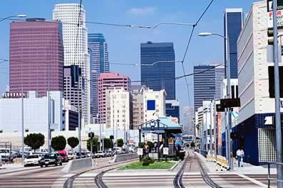 photo of a big-city downtown, with a light-rail station and tracks.