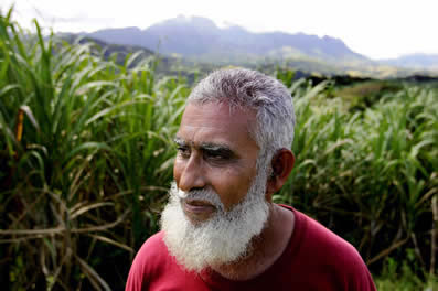 photo of a bearded man in front of some sugarcane