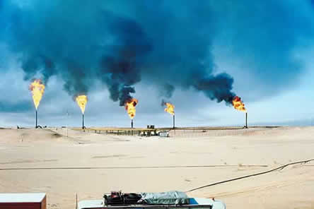 photo of a refinery with flames coming from towers in a barren landscape. the sky is darkened by the smoke.