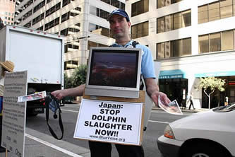 photo of a man wearing a video screen showing dolphin slaughter, handing leaflets to a crowd