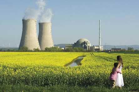 photo, reactor cooling towers in background; flowery field and frolicking children in foreground