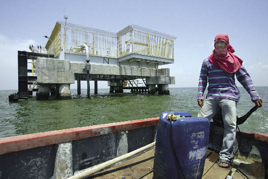 photo of man on the deck of a boat, a plastic container of petrol fueling it; a drilling platform in the water behind him