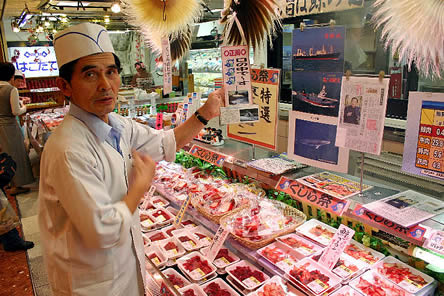 photo of a butcher, lots of red meat and japanese script in the case before him