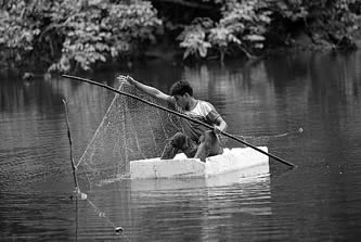 photo of a young man fishing from a raft made of styrofoam packaging