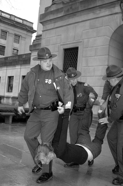 photo of uniformed people carrying a handcuffed young woman, head down away from a building