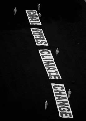 photo of people laying a huge banner that reads: coal fuels climate change