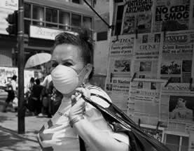 photo of a woman wearing a filter mask on a street corner