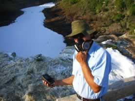 photo of a man in a respirator standing on a river beach, he is holding a scientific measuring meter