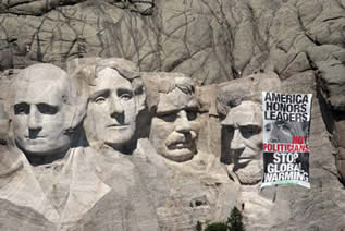 photo of Mt. Rushmore, banner hung on it that reads: America Honors Leaders, Not Politicians. Stop Global Warming