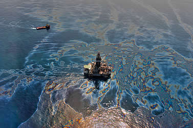 aerial photo of an oil rig at sea, large swath of rainbow oil flowing from it