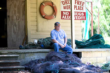 photo of a man sitting on a porch, surrounded by fishing nets. near a sign on the wall behind him that reads, drug-free workplace, hangs a life ring