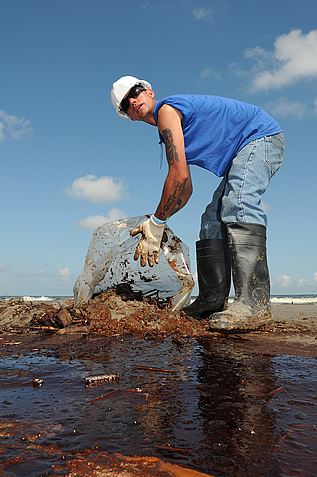 photo of a worker bagging oily debris