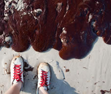photo of someones shoes standing on sand close to a large mass of spilled goo, oil