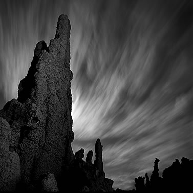 photo of rocky hoodoos under a night sky, eerily lit clouds