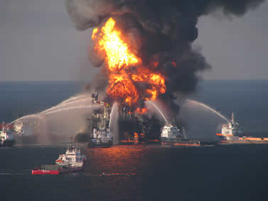 photo of an oil rig burning at sea, surrounded by fireboats spraying water without apparent effect