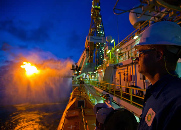 photo of a man standing on an industrial ship watching a fire at sea