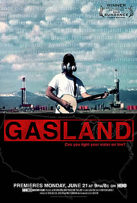 movie poster thumbnail, photo of a man wearing a gas mask playing a banjo, drilling rigs in the background