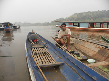 photo of a man sitting in a wooden boat, a river and other similar boats