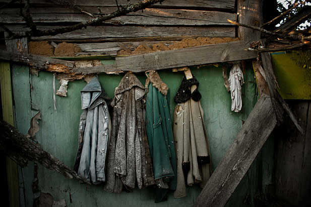 photo of a ruined wall with tattered winter coats hanging from it in a row