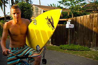 photo of a young man with a surfboard on a bike