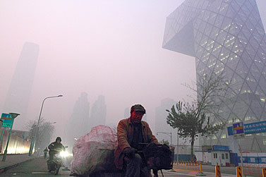 photo of a man on a bicylcle in Beijing, the air is thick with pollution