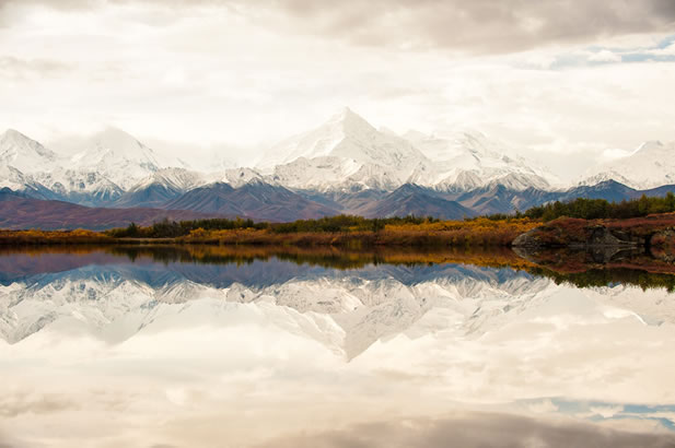 photo of a giant mountain range reflected in a pond