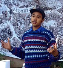 photo of a young man speaking, a fantastic artwork behind him
