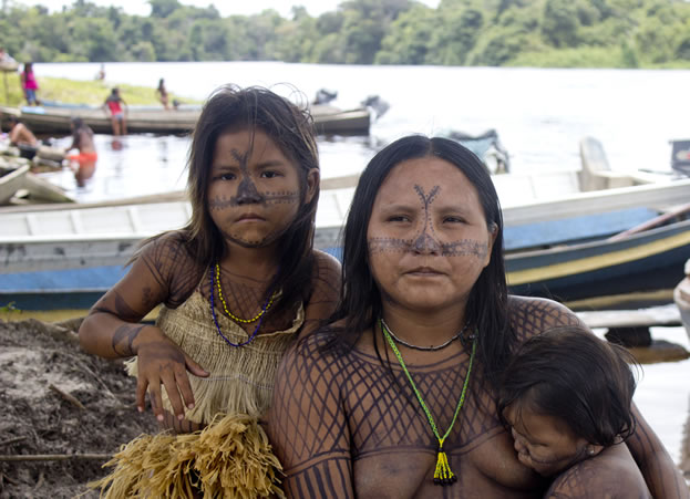 photo of a woman and a child, tribal-style markings or tattoos on their faces and arms - a busy river scene in the background