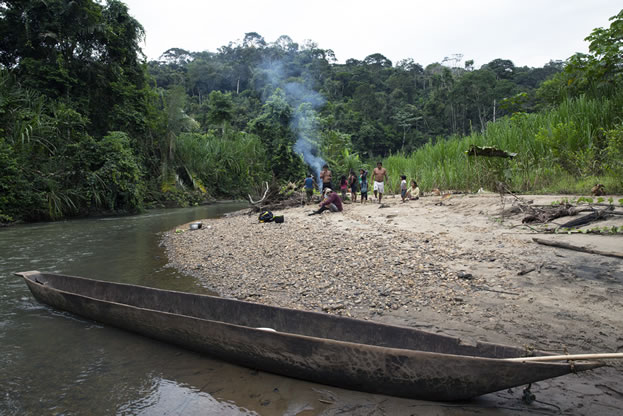 photo of a dugout canoe on a river beach in a tropical forest, people nearby