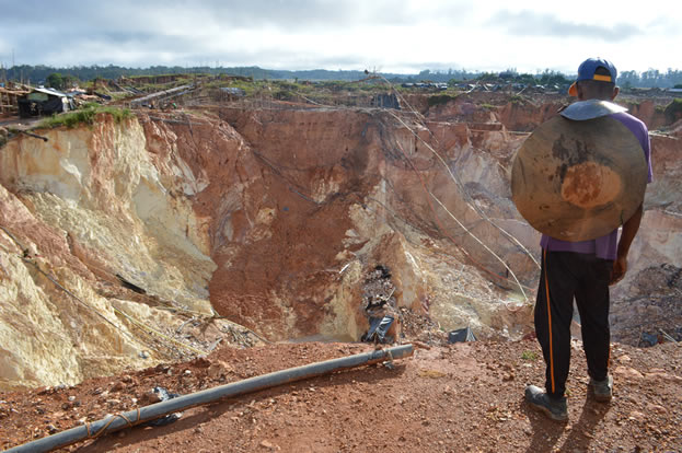 photo of a man standing on the edge of a pit mine