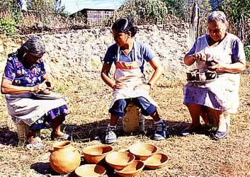 elder women and a young woman working with unfired pottery