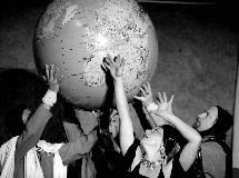 photo of people in various costumes holding a large globe