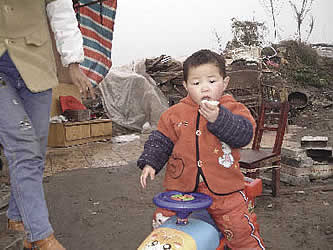 photo of a small boy, with some toys, and wreckage behind