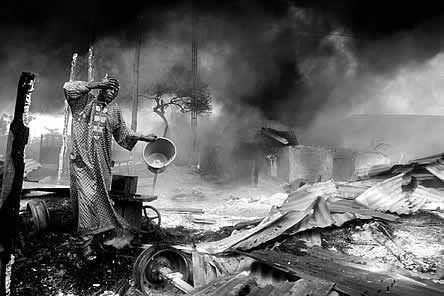 photo of a man splashing water on his face in a scene of smoke and fire and rubble