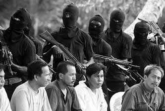 photo of several unhappy-looking people sitting with gun-toting masked people behind them