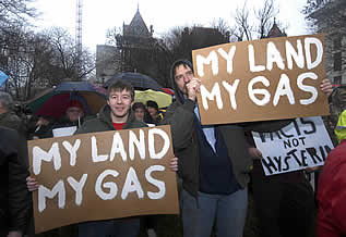 photo of people standing outside with signs which read: my land, my gas