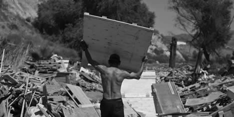 photo of a man carrying a sheet of plywood out of a pile of like objects
