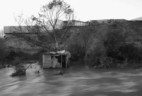 photo of a shack built at the waterline of a creek, gleaming offices above the bank