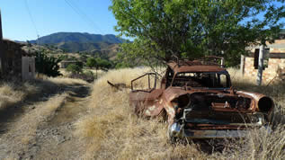 photo of an outdoor scene with a junked car and abandoned building