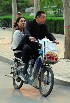 photo of a man and woman on an electric bike riding along a street