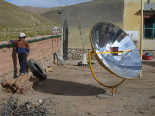 photo of a solar concentrating oven watched by a small child in a backyard