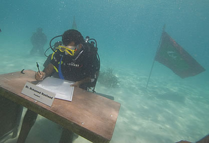 photo of a diver underwater at a desk appearing to sign papers; the desk has a name placard for Dr. Mohammed Nasheed, president. A flag flies in the water nearby.