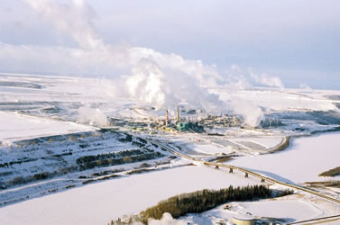 photo from above a snowy industrial landscape, a ice-covered river in the foreground, steam rising from smokestacks behind