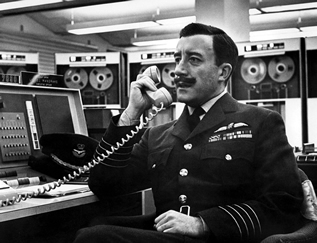 still from the movie, Dr. Strangelove depicting a uniformed man takling into a telephone in front of a bank of ancient computers