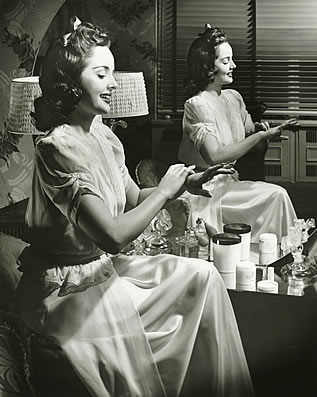 retro-stylized photo in sepia tones of a woman applying cosmetics in front of a mirror, she is smiling and the jars have no labels