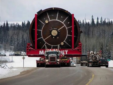 photo of an enormous truck with a gargantuan load driving on a small snowy road