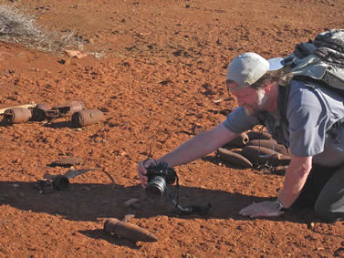 photo of a man on a volcanic soil, taking a photo close-up of an unexploded weapon